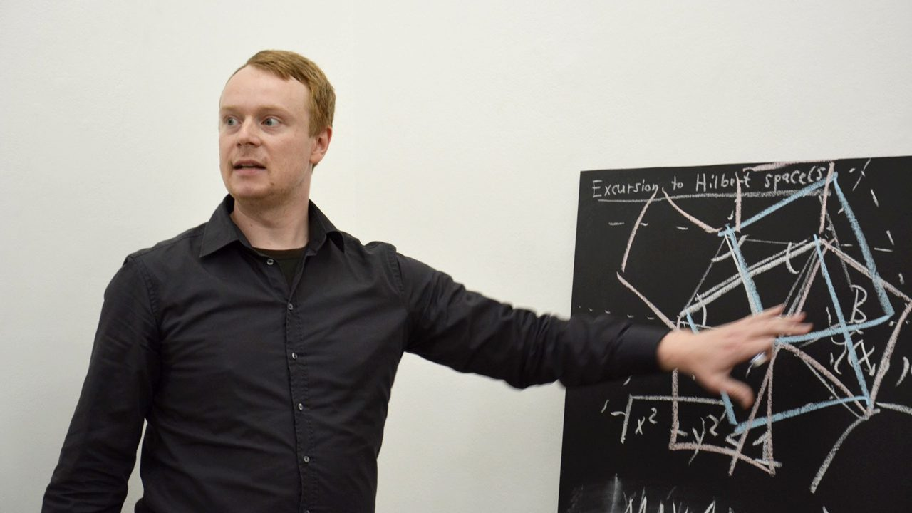 "Jonas Tölle during an artistic performance involving mathematics (in particular, Hilbert space theory), at the group exhibition ""No Lightning Strikes the Nettle"" taking place at the showroom Hilbertraum, Berlin-Neukölln (picture taken by Tiina Rajamäki)."